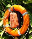 Lifebuoy orange with rope at front of trees Royalty Free Stock Photography