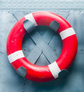 Lifebuoy red attached to a metal ship wall Royalty Free Stock Image