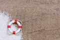 Lifebuoy with sand on wood Stock Photography