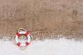 Lifebuoy with sand on wood Stock Photo
