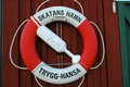 Lifebuoy sweden a life buoy hangs on a house in the swedish arcipelago classic trygg hansa saftey buoy Stock Images