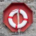 Lifebuoy on wall, red, white Royalty Free Stock Photo