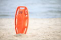 Lifeguard beach rescue equipment life saving orange preserver tool red plastic buoyancy aid in the sand Royalty Free Stock Image