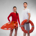 Lifeguard couple with rescue equipment accident prevention and water young men and women on duty holding ring buoy float lifesaver Royalty Free Stock Photos