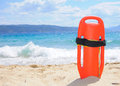 Lifeguard s buoy on the beach in sand with waves crashing into in background Royalty Free Stock Photography