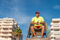 Lifeguard sitting high up on his chair watching the beach Royalty Free Stock Photos