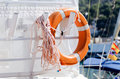 Lifesaving ring on yacht personal flotation device aft with rope Royalty Free Stock Photo