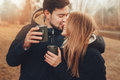 Lifestyle capture of happy couple drinking hot tea outdoor on cozy warm walk in forest autumn Stock Image