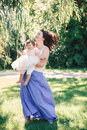 Lifestyle group portrait of smiling white Caucasian brunette mother holding hugging daughter in pink dress dancing