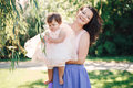 Lifestyle group portrait of smiling white Caucasian brunette mother holding hugging daughter in pink dress Royalty Free Stock Photo