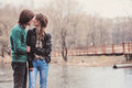 Lifestyle outdoor capture of young loving couple on the walk in early spring rainy day Royalty Free Stock Photo