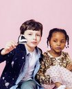 Lifestyle people concept: diverse nation children playing together, caucasian boy with african little girl holding candy Royalty Free Stock Photo