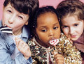 Lifestyle people concept: diverse nation children playing together, caucasian boy with african little girl holding candy