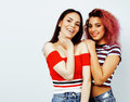 Lifestyle people concept: two pretty stylish modern hipster teen girl having fun together, diverse nation mixed races