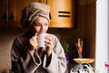 Lifestyle portrait of a beautiful young girl drinking morning coffee in her kitchen Royalty Free Stock Photo