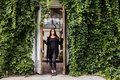 Lifestyle portrait of girl wearing blank black t-shirt, jeans and coat posing against building covered with green leaves Royalty Free Stock Photo