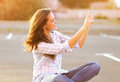 Lifestyle portrait happy beautiful woman doing a self portrait on the smartphone outdoors evening on sunset Royalty Free Stock Images