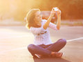 Lifestyle summer portrait happy pretty young woman selfie doing a self on the smartphone outdoors on evening light sunset Stock Photography