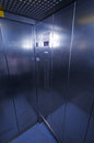 Lift inside empty wide angled of a metal clad elevator with light reflections Royalty Free Stock Photography