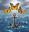 Lifting the burden business concept as a group of three monarch butterflies raising a heavy nautical anchor from a stormy ocean Stock Photos
