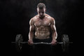 Lifting weights close up of young muscular man over dark background Royalty Free Stock Image