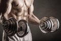 Lifting weights closeup of a muscular young man on dark background Royalty Free Stock Images