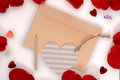 Light apricot envelope, heart card and pencil on white and rose petals background Royalty Free Stock Photo