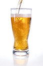 Light beer poured into glass on white Stock Image
