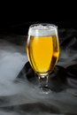 Light beer refreshing in a cold glass served on a dark bar with lingering fog Stock Photo