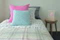 Light blue and pink pillow on sweet bedding and picture frame Royalty Free Stock Photo