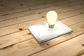 Light bulb and book on wooden table,book can help to answer of the question Royalty Free Stock Photo