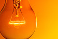 Light bulb close up glowing on orange background Royalty Free Stock Photo