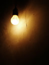Light bulb on a dark wall dusty incandescent background Royalty Free Stock Photography