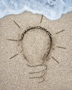Light bulb drawn on sand beach with white wave foam Royalty Free Stock Photo