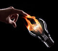 Light bulb with fire on black background Royalty Free Stock Photography