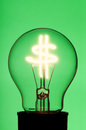 Light bulb with glowing dollar symbol on green background Royalty Free Stock Images
