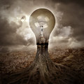 A light bulb is growing as a tree in a dark nature scene with roots for an energy or idea concept Stock Photos
