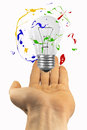 Light bulb hover over the hand with paint orbiting Stock Photo