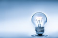 Light bulb incandescent with glowing filament blue toned image with copy space Stock Image