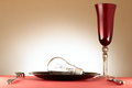 Light bulb on plate lit brightly in cutlery and wineglass red tablecloth Stock Photo
