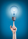 Light bulb on tip of finger Royalty Free Stock Images