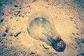 Light bulb was throw away on the beach. Royalty Free Stock Photo