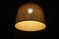Light bulb in a wicker lampshade shines dark room on dark background Stock Image