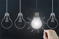 Light bulbs bright hanging against a row of drawn on a blackboard Stock Photos