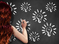 Light bulbs on chalkboard and girl Stock Image