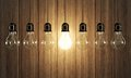 Light bulbs seven with glowing one on wooden background Royalty Free Stock Image