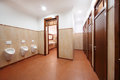 Light and clean public toilet with urinals red tiles wooden doors Stock Images