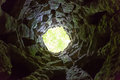 Light at the end of a narrow cave bottom view from round Royalty Free Stock Images