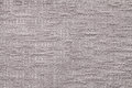 Light brown fluffy background of soft, fleecy cloth. Texture of plush furry textile, closeup.