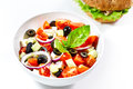 Light greek salad with fresh vegetables and burger in back Royalty Free Stock Photo